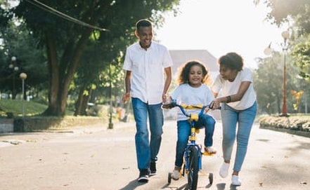 A photo of a man and woman teaching their young daughter to ride a bicycle on a sunny day