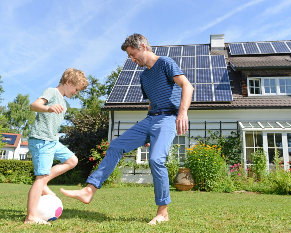 Photo of a man playing soccer with his son in front of a house with solar panels on the roof