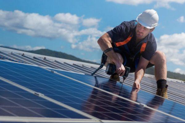A solar technician installing solar panels on a roof.