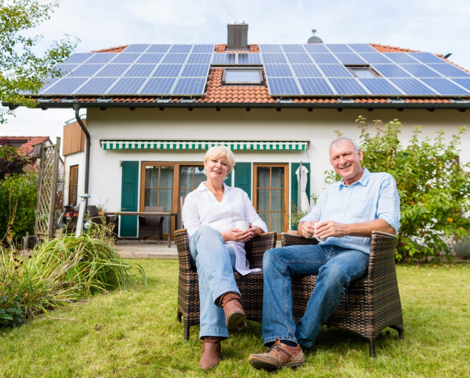 An elderly couple sitting in front of their home with solar panels on the roof