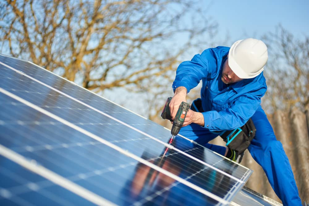 Solar panel installer working on a roof with a drill