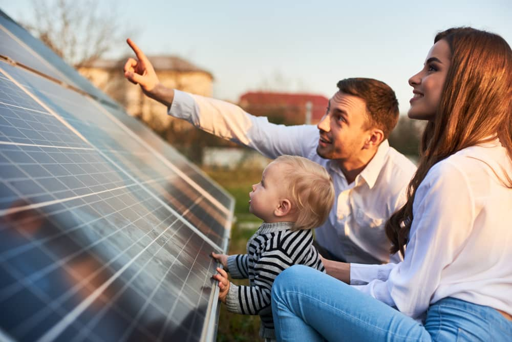 A couple with their baby crouching in front of a solar panel outdoors