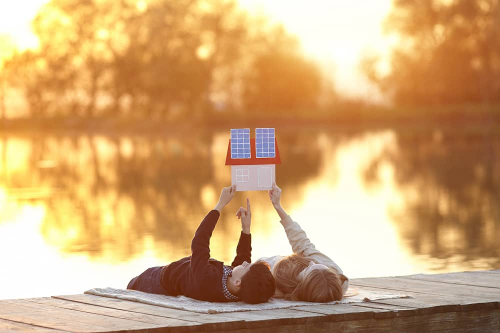 A parent and child lying on a lakeside dock holding up a small cutout picture of a house with solar panels