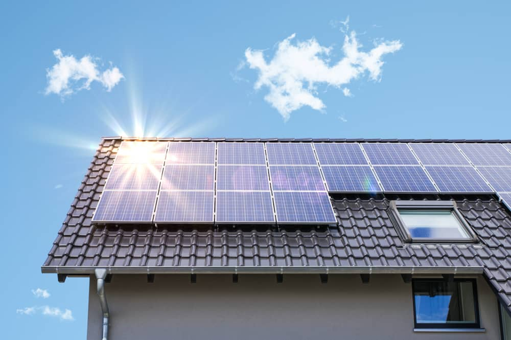 A photo of a house with solar panels on the roof on a sunny day