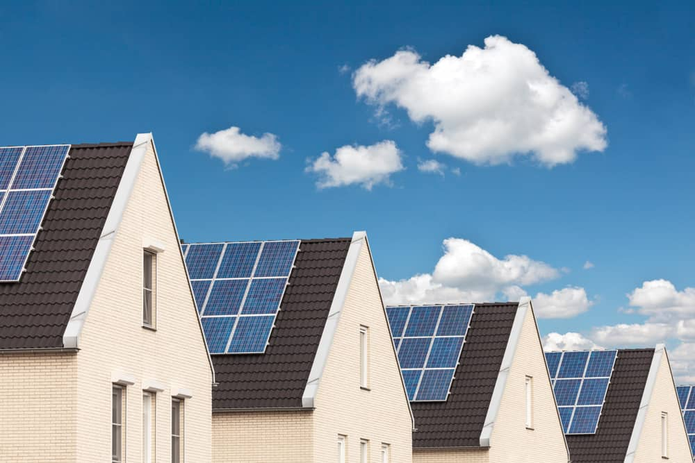 Photo of a row of houses with solar panels and a clear blue sky