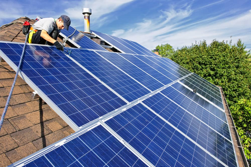 A technician working on the roof of a home with solar panels